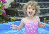 Young child laughing in a paddling pool.