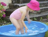 Young child in paddling pool.