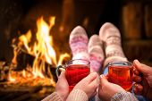 stock photo of hot couple  - Couple relaxing with mulled wine at romantic fireplace on winter evening - JPG