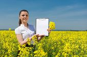 business woman with yellow flowers and blank sheet on field