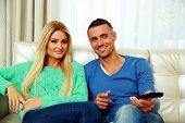Smiling young couple sitting on the sofa and watching TV