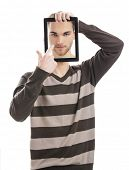 Good looking young man showing a tablet with is own picture on it