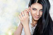 Portrait Of Young Brunette Woman Fixing Earring