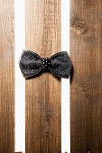 Black handmade bow tie over wood