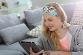 Student girl at home websurfing on digital tablet