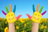 foto of sunflower  - Two smiley hands on a background of field of sunflowers and blue sky in sunny summer - JPG