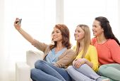friendship, technology and internet concept - three smiling teenage girls taking selfie with smartph