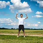 Healthy fit sportsman flexing his arms as he stands in an open rural field alongside a track in his