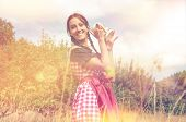 Smiling girl in traditional bavarian dirndl holds beer mug