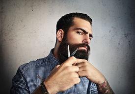 stock photo of hooligan  - Portrait of a man grooming his beard with scissors - JPG