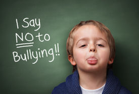 pic of school bullying  - Little boy standing up for himself and saying NO to bullying by blowing a raspberry at the bully in front of a blackboard at school - JPG