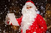 Santa Claus reading a letter outdoors