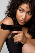 stock photo of young black woman  - Sexy black woman holding weapon gun closeup - JPG