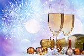 Glasses with champagne and bottle over sparkling holiday background