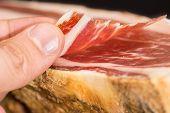 Side view of caucasian man finger taking Serrano ham slice