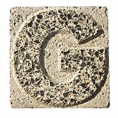 stock photo of carving  - Letter G carved in a concrete block  - JPG
