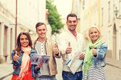 travel, vacation and friendship concept - group of smiling friends with city guide and map showing thumbs up in the city