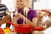 Closeup photo of cheese fondue with friends around.