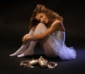 Pretty young ballet dancer sitting on floor, resting, smiling, looking at camera.
