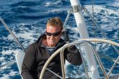 picture of sails  - Cheerful skipper on the helm of sailing boat - JPG
