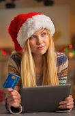 Portrait Of Thoughtful Teenager Girl In Santa Hat With Credit Card Using Tablet Pc