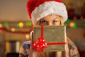 Teenage Girl In Santa Hat Hiding Behind Christmas Gift
