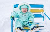 Baby Boy Sitting On Bench In Park In Winter