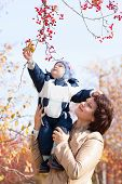 Young Mother Woman Girl Holding Baby Kid Son On Autumn Berries Background