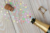 Overhead of a bottle of champagne with the cork popping on a rustic wood table. The spray from the bottle is stars of various sizes. With copy space it is perfect for New Years projects.