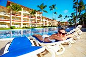 Woman relaxing near the pool. Vacation at caribbean resort