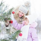 Happy mother and child decorating christmas tree outdoor wintertime