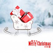 Wooden toy sledge with Christmas gifts on winter background as greeting card