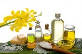 spa supplies with branch orchid, oil, yellow candle ,soap salt on banana leaf