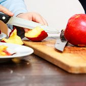 foto of unawares  - Child little boy playing dangerous game with a kitchen knife cut apple making salad at home - JPG
