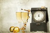 Vintage photo of glasses with champagne, clock close to midnight and Christmas balls on sparkling holiday background