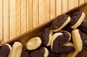 picture of pastarelle  - Mini Eclairs in a wooden plate on a wooden table - JPG