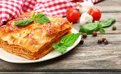 Portion of tasty lasagna on wooden table