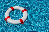 stock photo of crisis  - an emergency tire floating in a pool - JPG