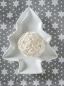 Christmas string ball ornament on white tree-shaped plate