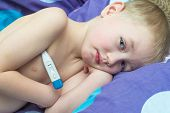 Boy Grip patient lying in bed with a thermometer