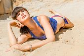 Relaxed Girl On A Sandy Beach For Sunbathing With Eyes Closed