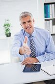 Happy businessman offering his hand in his office
