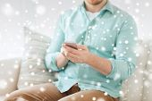 communication, business, home and technology concept - close up of man with smartphone texting message sitting on couch at home