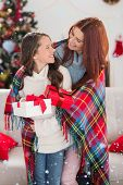 stock photo of blanket snow  - Festive mother and daughter wrapped in blanket with gifts against snow falling - JPG