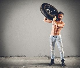 picture of muscle-car  - Seductive car mechanic working on a tire - JPG