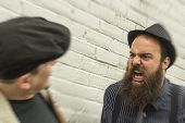 stock photo of yell  - Crazy angry bearded man yells in the face of a passerby - JPG