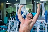 image of exercise  - Fit man exercising at the gym on a machine - JPG