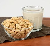 foto of milk glass  - A glass of cashew milk with a bowl of cashews on a brown tablecloth - JPG