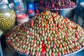 stock photo of pimiento  - Piramidal heap of green olives and red pepper in a Sicilian public market - JPG