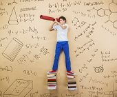 image of frot  - Cute little boy learning playfully in frot of a big blackboard - JPG